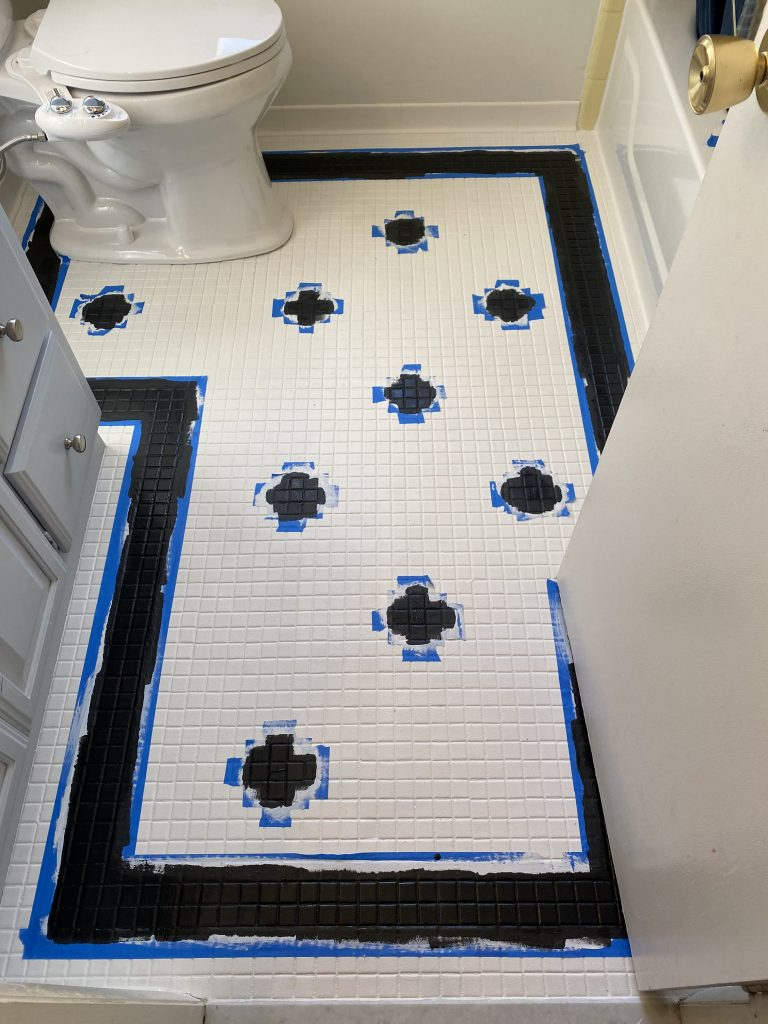 Painted coat of black Rustoleum floor paint to make design on tile